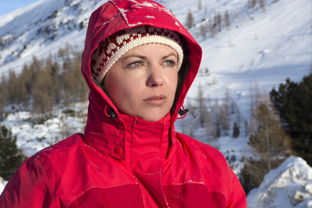 Woman with red outdoor jacket looks into the distance in the snowy mountains photo