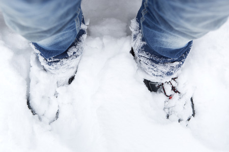 wintery snowy: Closeup of snowy mountain shoes and blue jeans
