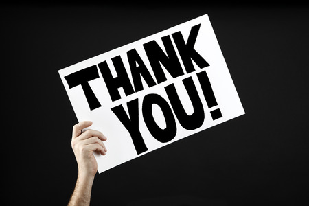 Man holding poster with thank you in front of a black background 写真素材