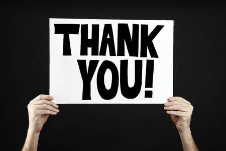 Man holding poster with thank you in front of a black background Stock Photo