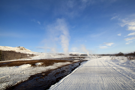 geysers: Several Geysers in a snowy winter landscape with blue sky in Iceland