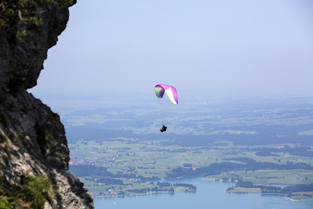 paraglider: Paraglider flying over Bavarian mountains in summer Stock Photo
