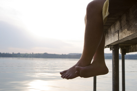 closing time: Legs on a dock in the evening sun