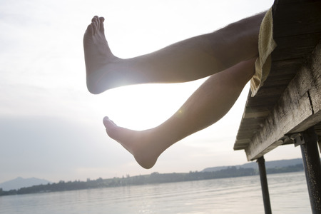 Man on a dock holding his feet in the air in the evening sun
