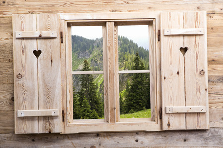 Wooden window with summery mountain as reflections