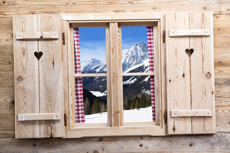 Wooden window with snowy mountains as reflections