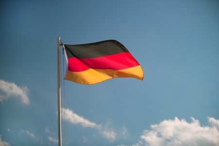 bandera de alemania: Bandera de Alemania en frente de un cielo azul en el viento Foto de archivo