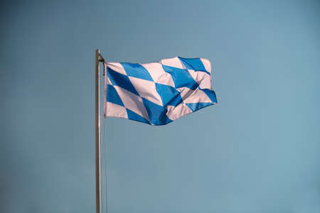 raise the white flag: Bavarian flag in front of a blue sky