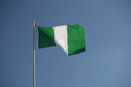 Nigerian flag in front of blue sky in the wind