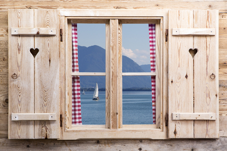 Wooden window with a lake and mountains as reflections
