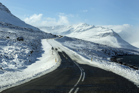 wintertime: Snowy road with volcanic mountains in wintertime, Iceland