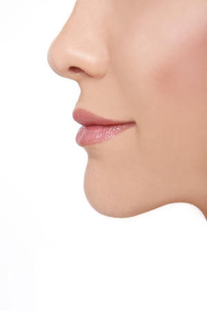 plastic surgery: Profile of a young beautiful woman in front of a white background