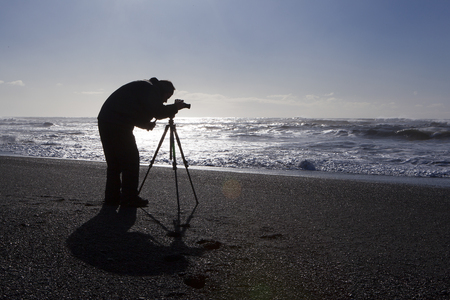 sight seeing: Photographer at black sand beach in Vik, Iceland, wintertime Stock Photo