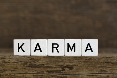 karma: The word karma written in cubes on wooden background Stock Photo