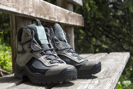 hiking shoes: Grey hiking shoes on a bench, summertime Stock Photo