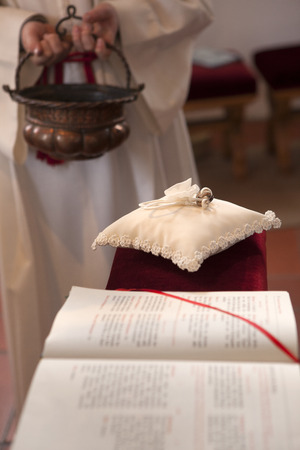 catholic wedding: Wedding rings on a white pillow in church Stock Photo