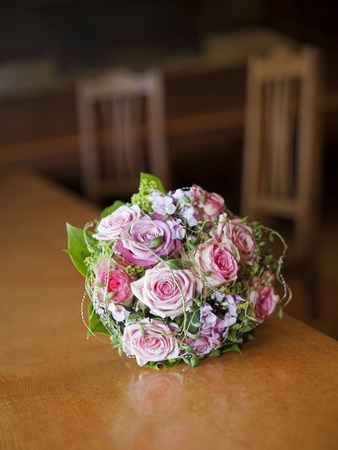 purple dress: Bridal bouquet with colorful roses on a table