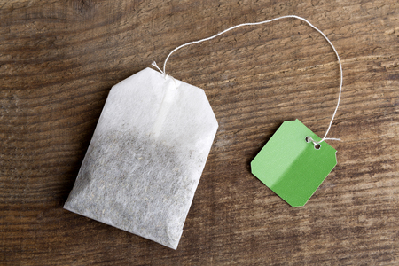 sniff: Closeup of green teabag on wooden background