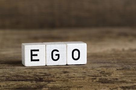ego�sta: La palabra ego escrito en cubos en un fondo de madera