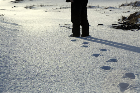 footsteps: Footsteps of a man with black trousers in the snow