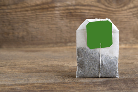 teabag: Closeup of green teabag on wooden background