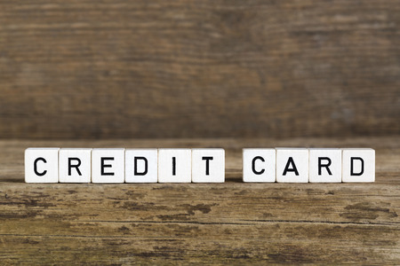 savety: The word credit card written in cubes on wooden background