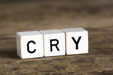 doleful: The word cry written in cubes on wooden background Stock Photo
