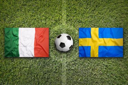 bandera italia: banderas de Italia vs Suecia en el campo de fútbol verde Foto de archivo
