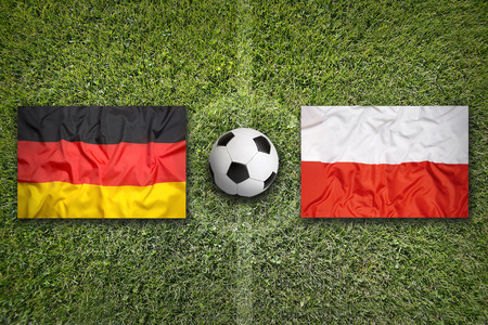 opponents: Germany vs. Poland flags on green soccer field Stock Photo