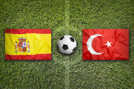team sports: Spain vs. Turkey flags on green soccer field