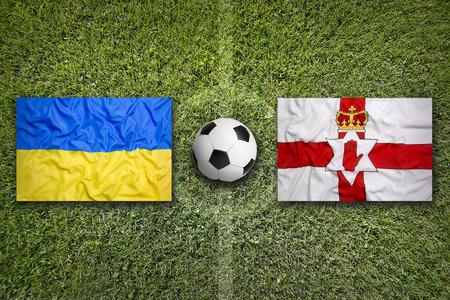 northern ireland: Ukraine vs. Northern Ireland flags on green soccer field