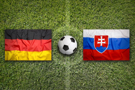 Germany vs. Slovakia flags on a green soccer field Stock Photo