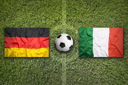 Germany vs. Italy flags on a green soccer field Standard-Bild