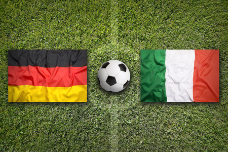 Germany vs. Italy flags on a green soccer field Stock Photo