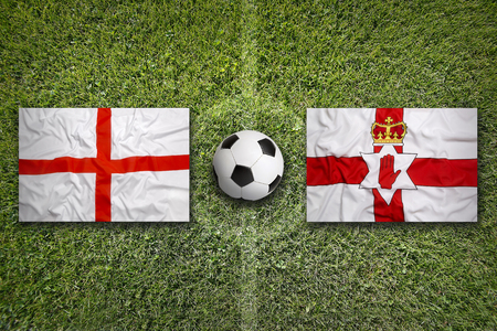 northern ireland: England vs. Northern Ireland flags on a green soccer field