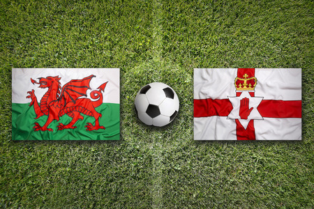 northern ireland: Wales vs. Northern Ireland flags on green soccer field