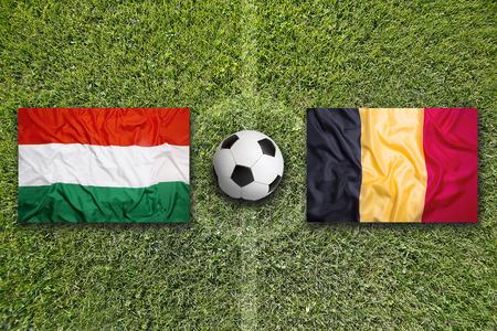 flag banner: Hungary vs. Belgium flags on green soccer field Stock Photo