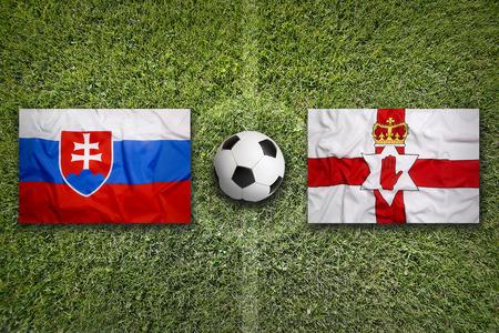 northern ireland: Slovakia vs. Northern Ireland flags on green soccer field