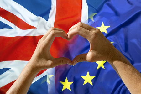 Hands heart symbol, exit Great Britain from European Union flags in background