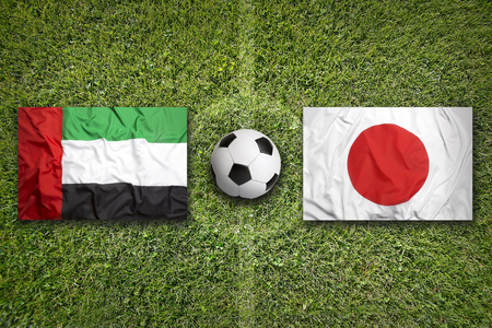arab flags: United Arab Emirates vs. Japan flags on green soccer field
