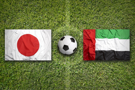 arab flags: Japan vs. United Arab Emirates flags on green soccer field