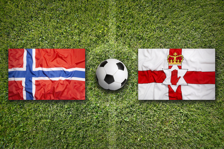 northern ireland: Norway vs. Northern Ireland flags on green soccer field Stock Photo