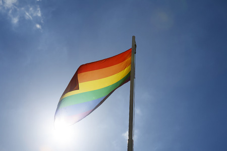 open minded: Rainbow flag on a flagpole in front of blue sky