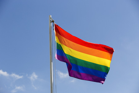 sexually: Rainbow flag on a flagpole in front of blue sky