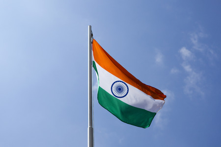 National flag of India on a flagpole in front of blue sky