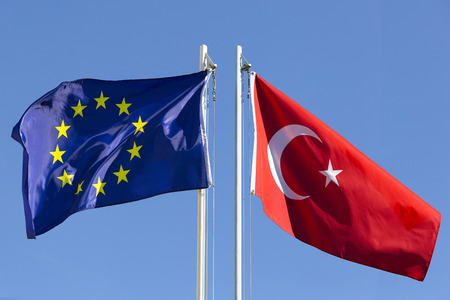flagpole: European Union flag and flag of Turkey on flagpole in front of blue sky
