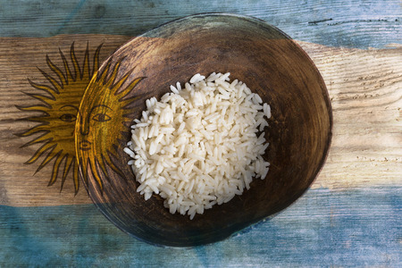 third world: Poverty concept, bowl of rice with Argentine flag on wooden background Stock Photo