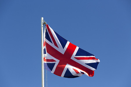 flagpole: UK flag on a flagpole in front of blue sky Stock Photo
