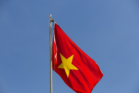 flagpole: National flag of Vietnam on a flagpole in front of blue sky