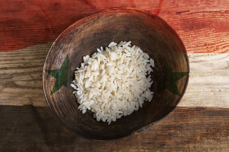 third world: Poverty concept, bowl of rice with Syria flag on wooden background